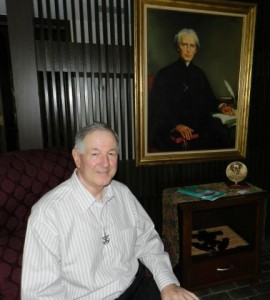 Bro. Bill Nick, CSC, under a portrait of Blessed Father Basil Moreau, CSC, founder of the Congregation of Holy Cross.